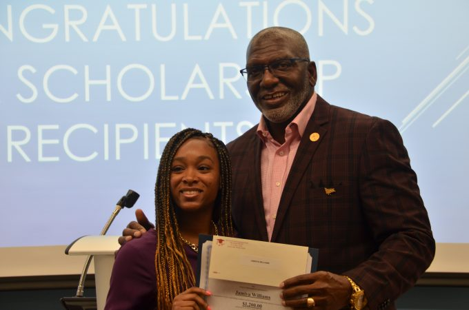 ILA President Vince Cameron presents a scholarship to a student