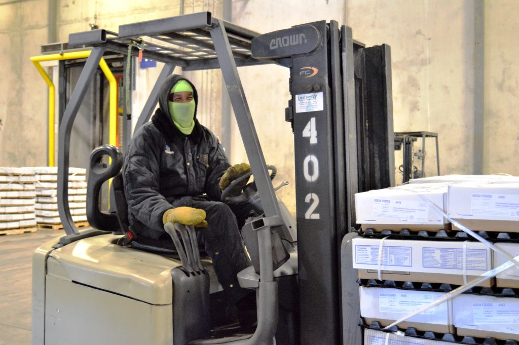 Worker on forklift moves product through the Seaonus Cold Storage warehouse.