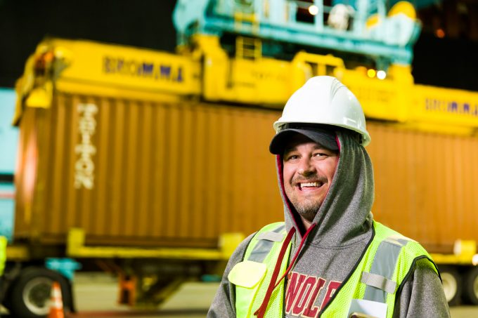 A dock worker standing in front of a container